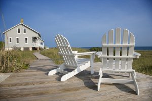 Two Adirondack style chairs sitting on a wooden deck, facing the shore. There is a large home in the background. Horizontal shot.
